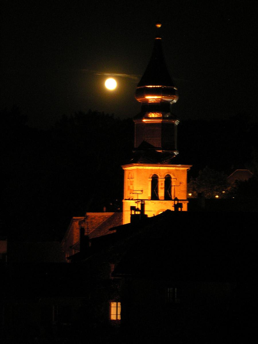 Pleine lune derrière le clocher de l'église d'Yvoire.