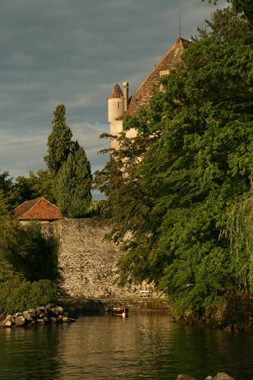 Une tourelle du château d'Yvoire apparaît discrètement derrière les feuillages des arbres.